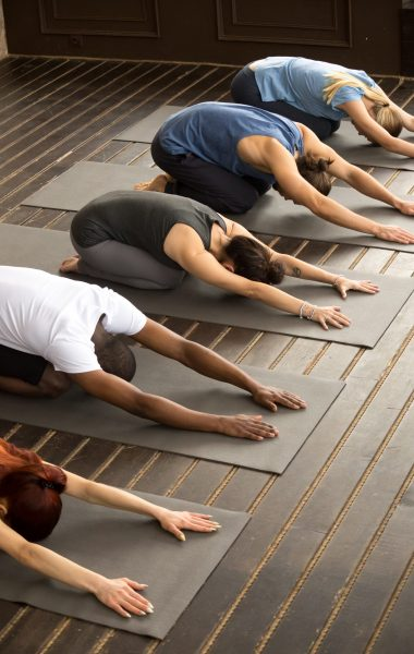 Group of young sporty afro american and caucasian people practicing yoga lesson stretching in Child exercise, Balasana pose, working out, indoor, studio background. Healthy lifestyle concept