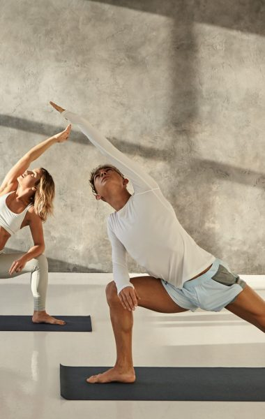 Young couple practicing yoga together. Indoor picture of handsome tanned guy on mat doing standing pose s to strengthen legs, stretching arms and looking up, blonde woman doing the same in background